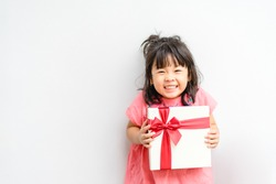 Little asian girl smile and holding red gift box on white background.child holding gift box on birthday.Merry christmas.present box.Asian child girl toddler baby smile surprise on her birthday.