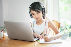 Little asian girl using laptop to learning at home and writing homework on notebook  homeschool concept
