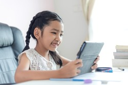 Little Asian girl using tablet and smile with happiness for education concept select focus shallow depth of field