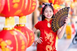 little Asian girl wearing red traditional Chinese cheongsam and holding a Fanningand lanterns with the Chinese alphabet Blessings written on it Is a Fortune blessing compliment decoration for New Year