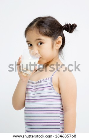 Little Asian girl with a glass of milk