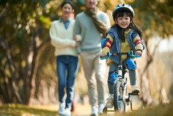 little asian girl with helmet and full protection gears riding bike in city park with parents watching from behind