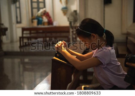 Little asian girl with praying at christ church. Kid asia girl closed her eyes, praying to peace with scripture bible. people hope, dreams concept. Foto stock ©