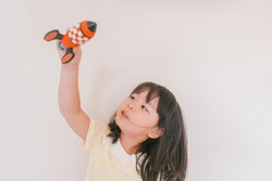Little asian girl with rocket. Child playing at home. Success, leader, Imagination, freedom and smart concept.