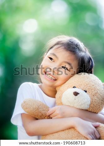 Little Asian girl with teddy bear in park.