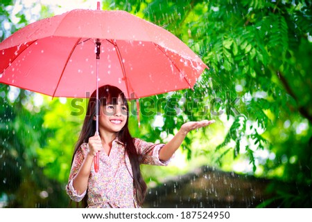 Little asian girl with umbrella in the rain