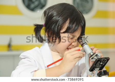 Little Asian kid looking into a microscope
