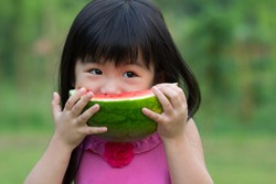 Little Asian kid with a piece of watermelon in park