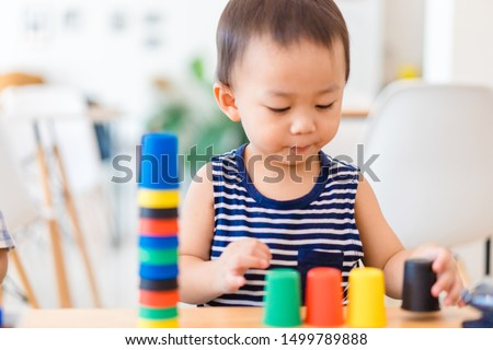 Little asian toddler boy playing stacking cups learning materials in a montessori methodology school being manipulated by children.Montessori classroom for the learning of children in mathematics. #1499789888