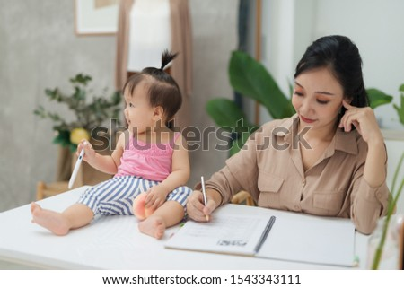 Little assistant. Little baby girl using pen while sitting on office desk with her mother in office #1543343111