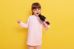 Little attractive girl with microphone singing her favorite song, looks at camera with opened mouth, wearing pale pink shirt, standing against yellow wall, small vocalist sings.