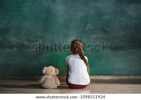 Little autistic girl with teddy bear sitting on floor at empty room. Autism concept. Conceptual image with little caucasian model at studio. Back view #1098551924