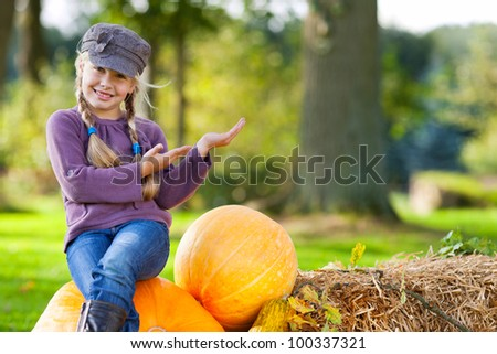 little autumn girl presenting copy space