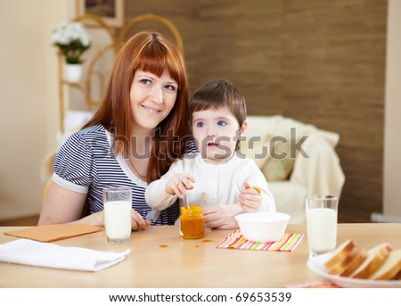 little baby at home sitting at the table and having meal