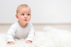 Little baby boy crawling on the floor and smiling, baby and white background,  banner copy space