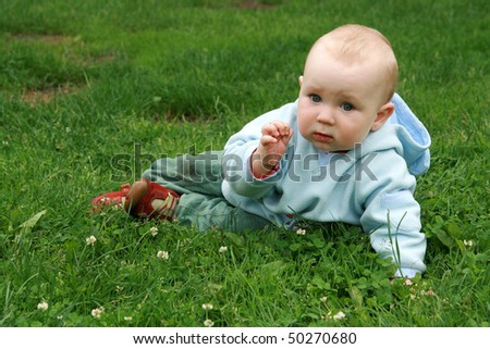 Little baby boy crawling on the grass. Baby learning to crawl.
