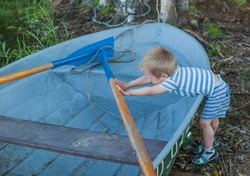 Little baby boy dressed in striped shorts and shirt, standing near metal boat and strongly pushing vessel's paddle  , playing with it on the shore of lake with birches and grass