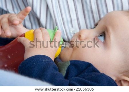 little baby boy drinking juice, with his father