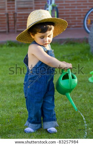 little baby boy gardener playing in his front yard