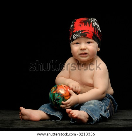 Little baby boy in sculled bandana with small ball next to black cap