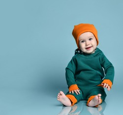 Little baby boy in stylish casual jumpsuit, hipster cap and barefoot sitting on floor and smiling over blue wall background. Trendy baby clothing and happy childhood concept