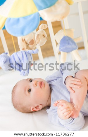 Little baby boy (4 months old) lying on crib and looking up to hanging toy, smiling. Toys are officially property released.