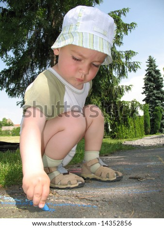 Little baby boy paint picture with blue chalk on the road