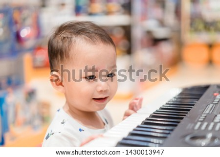 Little baby boy play keyboard and drum at home.Asian boy playing and singing happy moment in music time. #1430013947