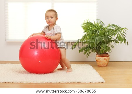 Little baby boy playing with big red ball