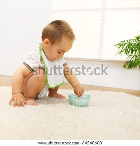 Little baby boy playing with food alone