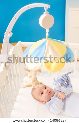 Little baby boy playing with hanging toy on crib. Toys are officially property released.