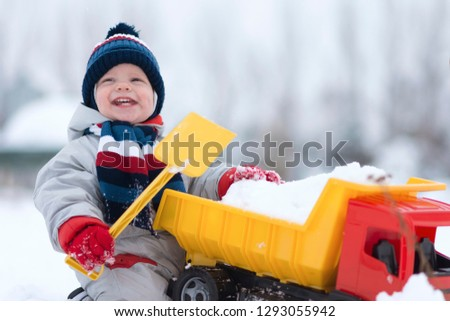 little baby boy playing with his favourite toy at the snowtime. A kid 15-23 month enjoy playfull,spending time in snow. A toddler  and his plastic truck at the winter games. Kids and toys concept #1293055942