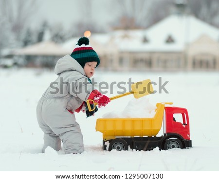little baby boy playing with his favourite toy at the snowtime. A kid 15-23 month enjoy playfull,spending time in snow. A toddler and his plastic truck at the winter games. Kids and toys concept. #1295007130
