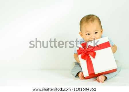 Little baby boy smile and holding red gift box on white background.child holding gift box.