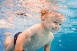 Little baby, boy swimming under water in paddling pool. Diving baby. Learning infant child to swim. Enjoy of swimming and bubbles.