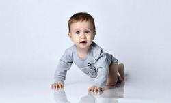 Little baby boy toddler in grey casual jumpsuit and barefoot crawling on floor, smiling and looking up over white wall background. Trendy baby clothing, first steps and happy childhood concept