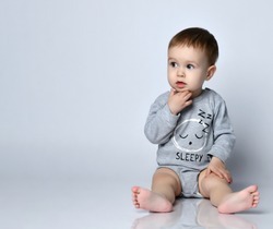Little baby boy toddler in grey casual jumpsuit, cap and barefoot sitting on floor and feeling interested looking aside over white wall background. Trendy baby clothing and happy childhood concept