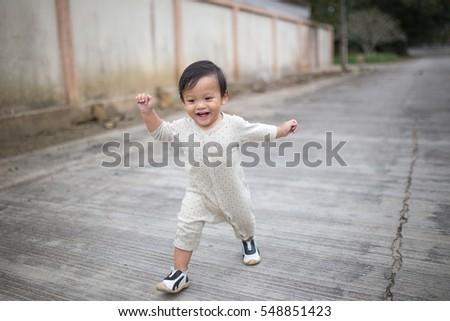 Little baby boy walking along the street. #548851423