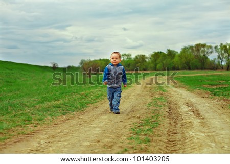 little baby boy walking country road on cloudy sky background