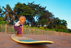 Little baby boy - young surfer stand on surf board with fun on sunset sea sand beach. Family lifestyle, people outdoor water sport lessons and swimming activity on summer surf camp vacation with child