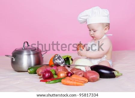 Little baby cook in studio - stock photo