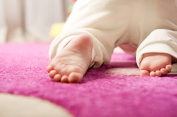 Little baby crawling on the pink carpet. Rear view