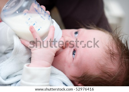 little baby drinking milk from a bottle with baby bib