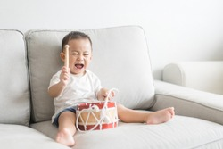 Little baby drummer boy playing and hitting the drum set at home.Asian boy playing and singing happy moment in music lesson time.Child development and Executive function in child concept.