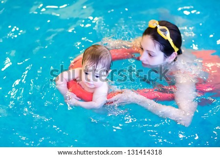 Little baby enjoying swimming pool with her mother