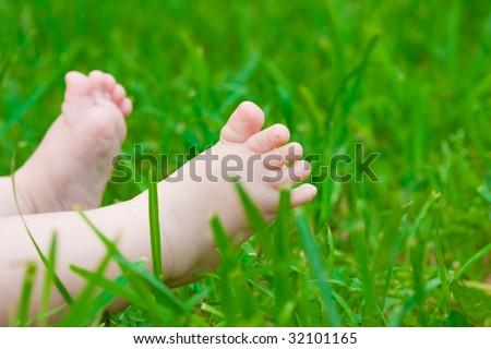 Little baby feet on fresh green grass outdoors