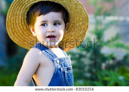 little baby gardener whith a hat teasingly smiling and enjoying his job
