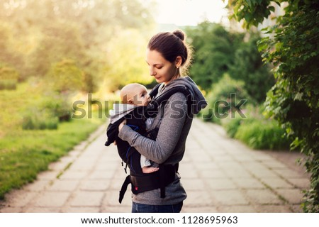 Little baby girl and her mother walking outside during sunset. Mother is holding and tickling her baby, babywearing in the ergo carrier
