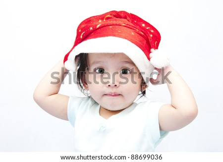 Little baby girl and Santa's hat - stock photo