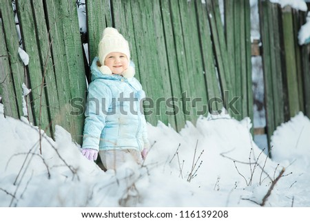 Little baby girl at winter in the forest